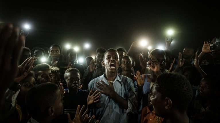 Sudański nastolatek recytuje wiersz na proteście w Chartumie oświetlany przez światło smartfonów