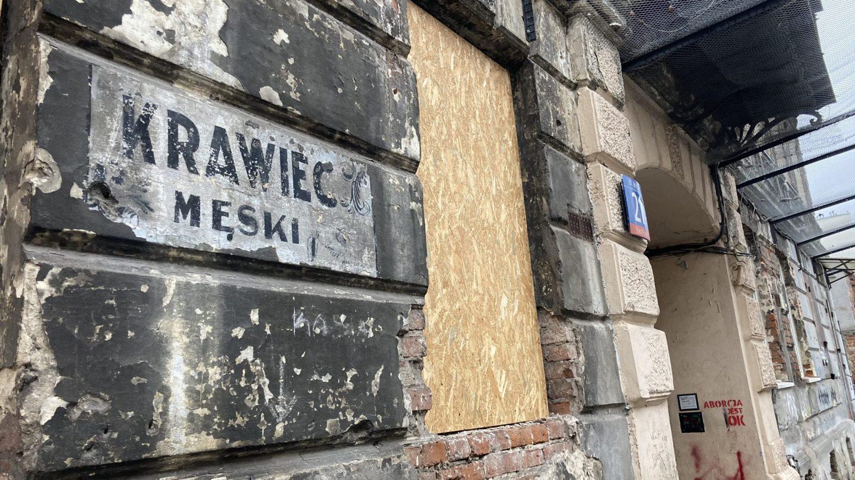 napis krawiec męski na budynku starej kamienicy