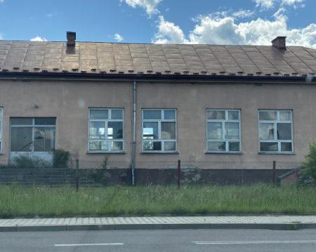 opustoszały budynek szkoły z wybitymi oknami