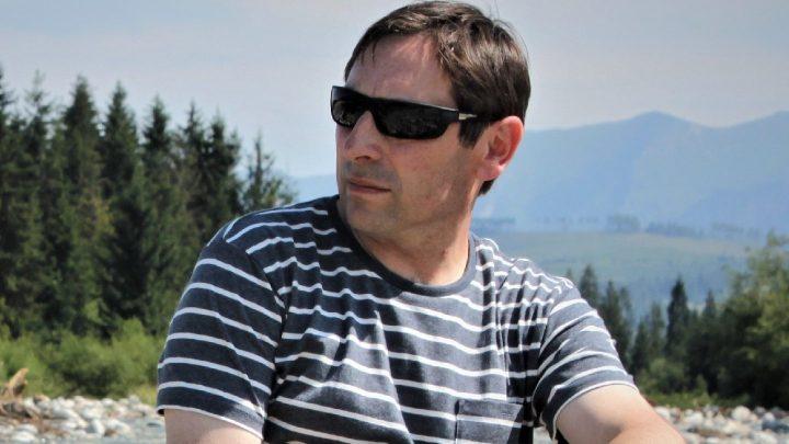 autor książki w ciemnych okularach siedzi nad potokiem w bieszczadach